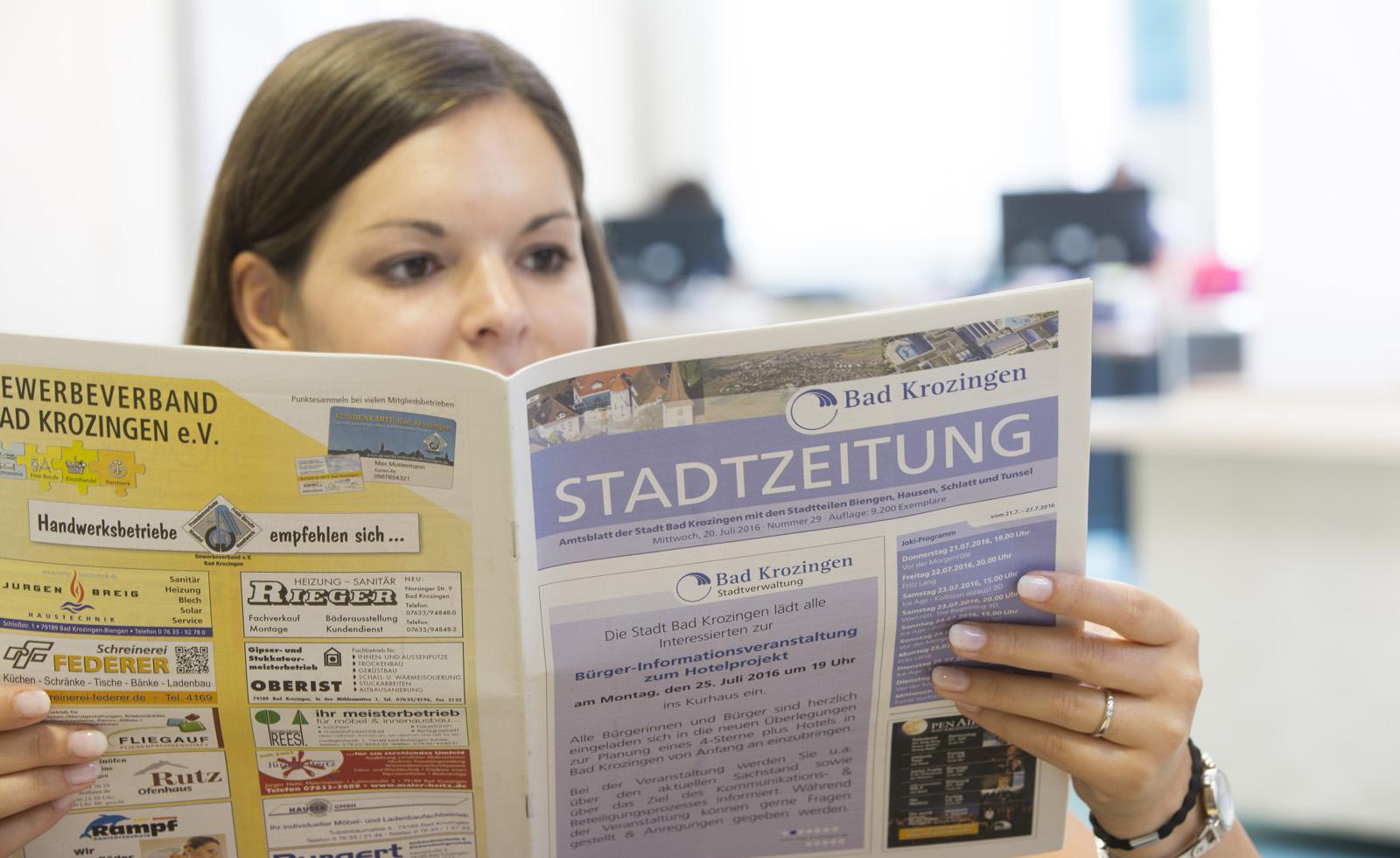 Bild von Frau mit Stadtzeitung