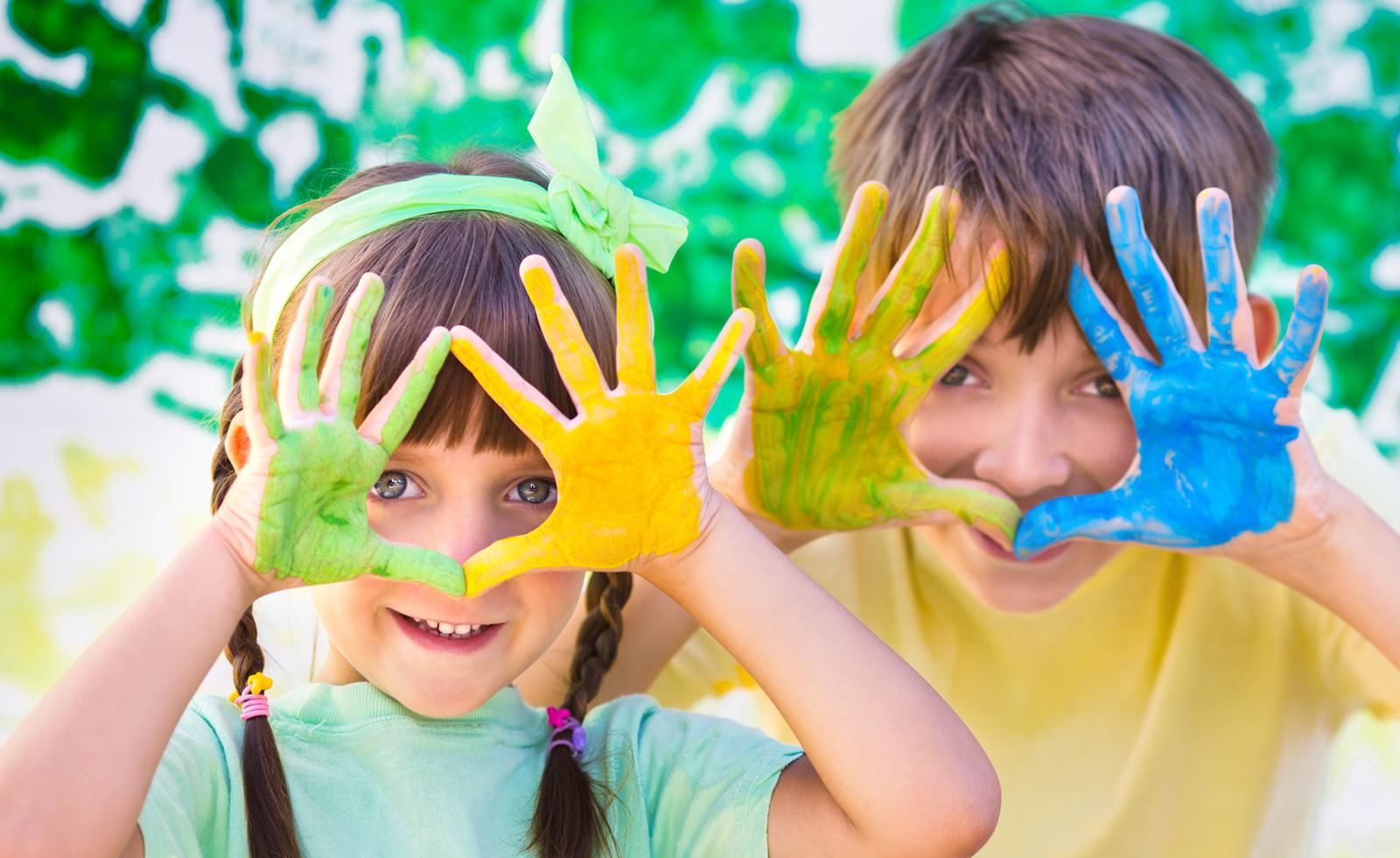 Drei Kinder spielen auf einer grünen Wiese